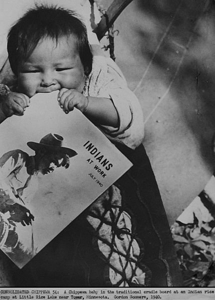 Original typed period caption: CONSOLIDATED CHIPPEWA 54: A Chippewa baby in the traditional cradle board at Indian rice camp at Little Rice Lake near Tower, Minnesota. Gordon Sommers, 1940.