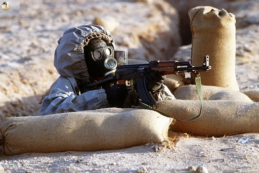 A Syrian soldier aims an AK-47 assault rifle wearing a Soviet-made, model ShMS nuclear–biological–chemical warfare mask. Unknown author - http://picasaweb.google.com/lh/photo/0JoLDPpw5WbYCMAmPsXL1g