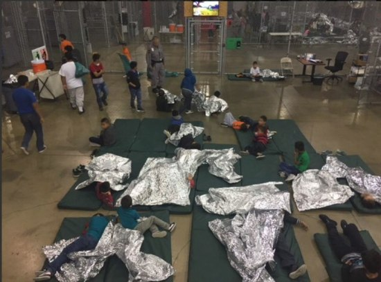 Detained children in a wire mesh compartment, showing sleeping mats and thermal blankets on floor. Photo provided by Custom and Border Protection to reporter on tour of detention facility in McAllen, Texas. Reporters were not allowed (BY WHAT RIGHT!?!) to take their own photos. Photo on 17 June 2018, provided by the U.S. Customs and Border Control.